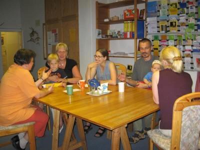 Foto von einer Elterngesprächsgruppe, an der drei Mütter, ein Vater, zwei Kinder und die Gesprächsleiterin teilnehmen