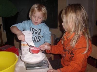 """Foto von der Veranstaltung """"Gemeinsam kochen"""", zwei kleine Mädchen sieben Mehl"""