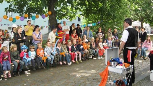 Foto von der Zaubervorführung während des SHIA-Kinderstraßenfestes, viele Kinder und Eltern folgen gespannt der Vorführung des Zauberers