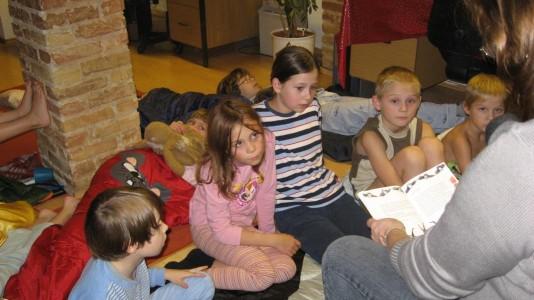 Foto von einer Lesenacht, Kinder lauschen der SHIA-Kollegin, die eine Geschichte vorliest