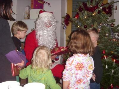 Foto von der Weihnachtsfeier für Eltern und Kinder 2013, der Weihnachtsmann verteilt unter dem Weihnachtsbaum Geschenke an die Kinder