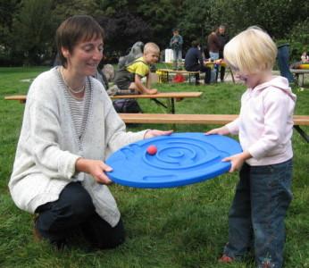 Foto von einer Frau mit Kind, die auf einer Wiese spielen
