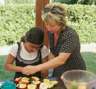 Mutter und Tochter beim Zubereiten von Obstsalat